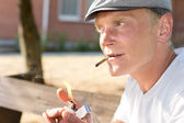 Positive thoughtful man lighting a brown cigarette — Stock Photo