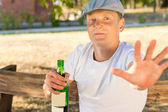 Ashamed man addicted to alcohol holding a bottle — Stock Photo