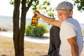 Happy drunk with his bottle of booze — Stock Photo