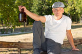Alcoholic sitting alone in the park with a bottle — Stock Photo