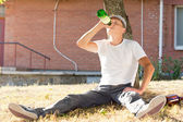 Alcoholic sitting drinking under a tree — Stock Photo
