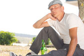 Depressed man sitting with a bottle of white wine — Stock Photo