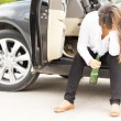 Drunk woman sitting in the door of her car — Stock Photo