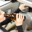 Drunk womimbibing as she drives — Stock Photo #32069917