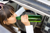 Woman drinking alcohol while driving a car — Stock Photo