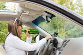 Woman driver drinking and driving her car — Stock Photo