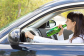 Inebriated female driver drinking alcohol — Stock Photo