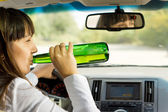 Intoxicated woman drinking and driving — Stock Photo