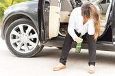 Drunk woman sitting in the door of her car — Stock Photo