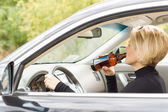 Woman driving along drinking alcohol — Stock Photo