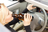 Drunk woman imbibing as she drives — Stock Photo