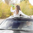 Woman standing up through a sunroof drinking — Stock Photo