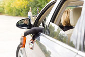Drunk female dangling a bottle outside the car — Stock Photo