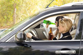 Two women driving a car while drinking — Stock Photo