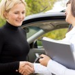 Saleslady congratulating a new car owner — Stock Photo #32092483