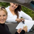Happy woman signing for her new car — Stock Photo