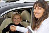Smiling saleslady congratulating the new owner — Stock Photo