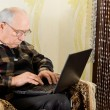 Senior man typing on his laptop computer — Stock Photo