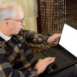 Senior man using a laptop computer — Stok fotoğraf