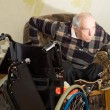 Disabled man changing from a chair to a wheelchair — ストック写真
