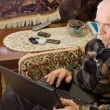 Senior man sitting working on a laptop — Stock Photo