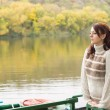 Young woman waiting at a tranquil river — Stock Photo