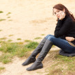 Wistful young woman sitting outdoors alone — Stock Photo
