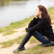 Lonely young woman sitting on a lake shore — Stock Photo