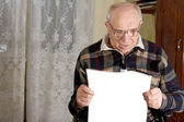 Delighted senior man reading the newspaper — Stock Photo