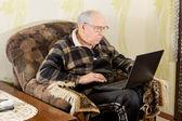 Elderly man surfing the internet on a laptop — Stock Photo