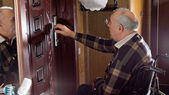 Man in a wheelchair checking his house locks — Stock Photo