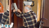 Senior man retrieving a newspaper through a door — Stock Photo
