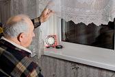Elderly man peering out through the window — Stock Photo