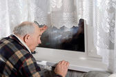 Senior man peering through a window at night — Stock Photo