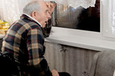 Elderly horrified man watching through a window — Stock Photo