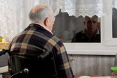 Elderly man in a wheelchair waiting at a window — Stock Photo