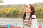 Attractive teenage girl sitting at a lake — Stock Photo