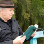 Senior man relaxing reading his book outdoors — Stock Photo #33716379