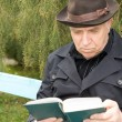 Portrait of an elderly man reading outdoors — Stock Photo