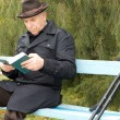 Elderly disabled man sitting outdoors reading — Stock Photo