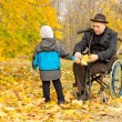 Stock Photo: Little boy with his handicapped grandfather