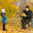 Disabled grandfather and child in an autumn park — Stock Photo