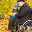Disabled man and his grandson enjoying autumn — Stock Photo