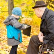 Stock Photo: Little boy showing his grandfather his tablet