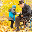 Young child with his disabled grandfather — Stock Photo #33814235