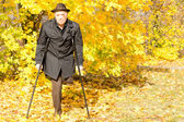 Handicapped elderly male amputee in a fall park — Stock Photo