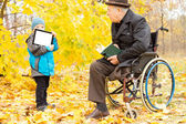 Youngster showing a disabled man a tablet-pc — Stock Photo