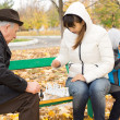 Attractive woman playing chess with an elderly man — Stock Photo