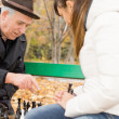 Senior man playing chess with his granddaughter — Stock Photo