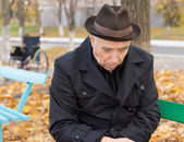 Sad lonely old man on a park bench — Stock Photo